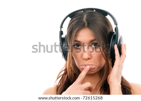 Attractive cheerful brunette woman listening and enjoying music in headphones, one hand finger touch mouth isolated on a white background - stock photo