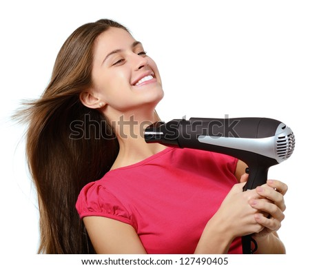 attractive cheerful teenager girl blows dry her hair with hairdryer, over white - stock photo