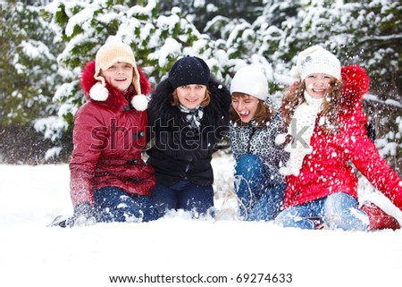 Attractive cheerful teenagers  throwing snow in park - stock photo