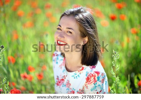 Attractive cheerful woman portrait on background of flowering meadow - stock photo