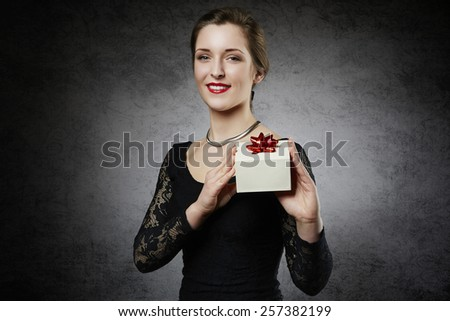 Attractive cheerful woman with gift box - stock photo