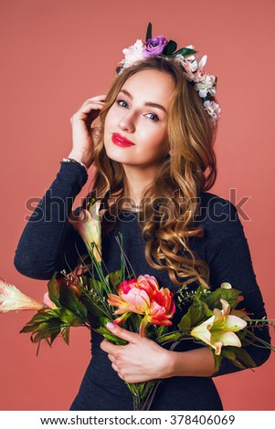Attractive cheerful young woman with beautiful curly long hair in flower wreath over  pink  background smiling. Close up studio portrait.  - stock photo