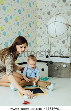 Attractive child with young mother draw at chalkboard indoors. Kid having fun at home. Boy in bowtie. - stock photo