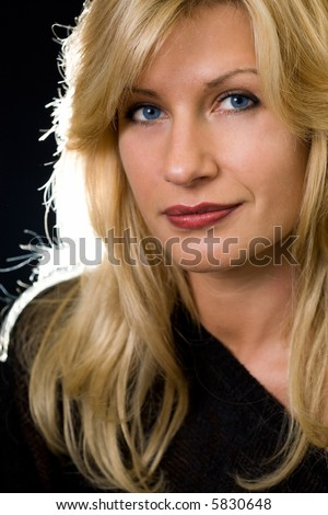 Attractive close up of face of a woman with long blond hair and blue eyes with serious expression over black
