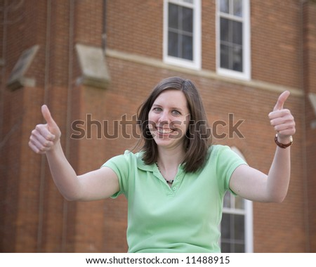 Attractive college student gives thumbs up - stock photo