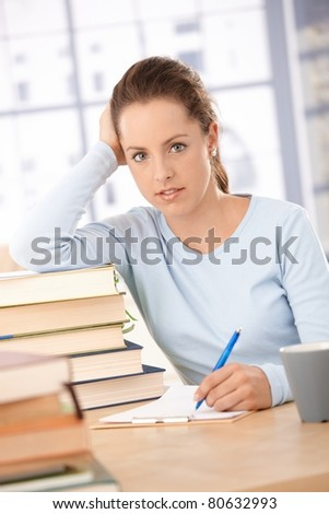 Attractive college student learning at home, smiling, leaning on books, sitting at table.?
