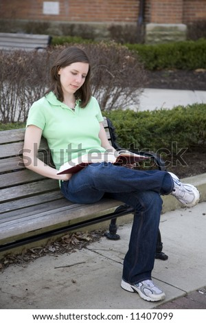 Attractive college student reading outside on a bench - stock photo