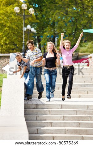 Attractive college students running and throwing their books - stock photo