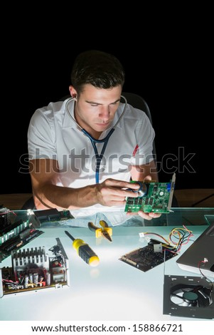 Attractive computer engineer examining hardware with stethoscope by night at his lit desk