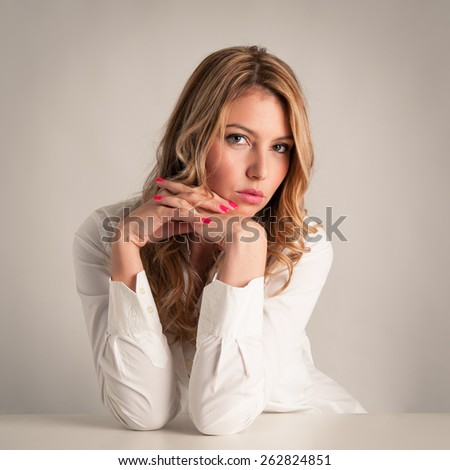 Attractive confident blonde woman against light beige background. - stock photo