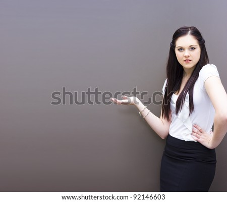 Attractive Confident Business Person Displaying Room For Text When Holding Out Empty Hand For Product Placement Or To Show A Sales Presentation With Copy Space - stock photo
