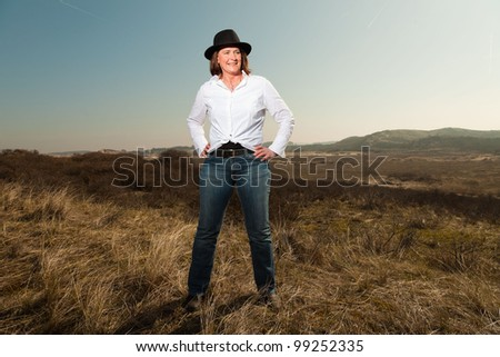 Attractive confident woman wearing a hat middle aged enjoying outdoors. Clear sunny spring day with blue sky. - stock photo
