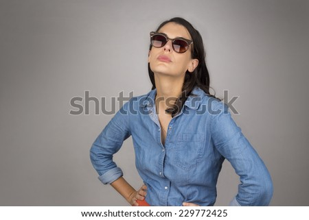 Attractive confident young woman with shoulder length brunette hair in dark glasses standing against a grey studio background with her hands on her hips, upper body with copyspace - stock photo