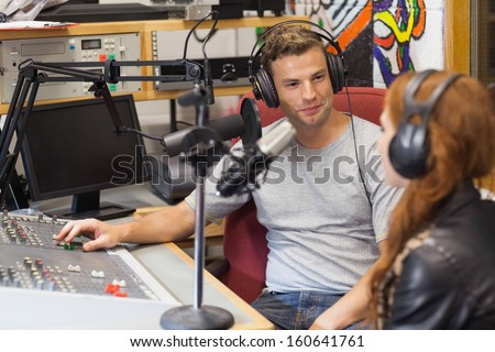 Attractive content radio host interviewing a guest in studio at college - stock photo