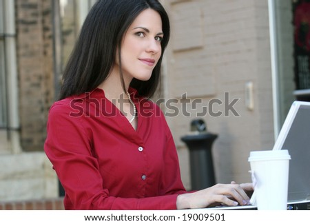 Attractive corporate, business woman working on her laptop outdoors with a cup of coffee or tea, in a city street - stock photo