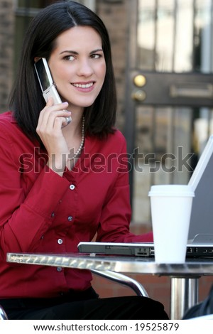 Attractive corporate, business woman working on her laptop outdoors, with a cup of tea, in a city street - stock photo
