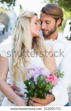 Attractive couple about to kiss each other on a sunny day in the city - stock photo