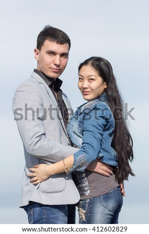 Attractive couple against of sky. Asian girl and european guy posing on background of sky - stock photo