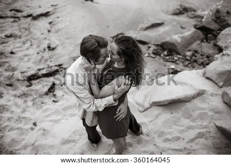 Attractive couple at beach loving embrace