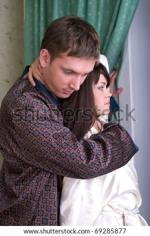 Attractive couple at home looking to the window - stock photo