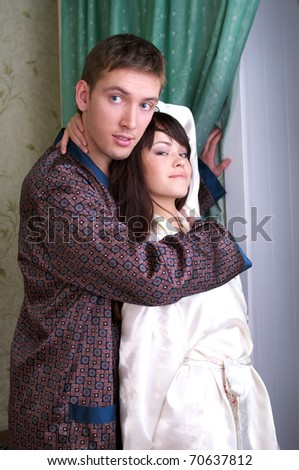 Attractive couple at home near to the window - stock photo