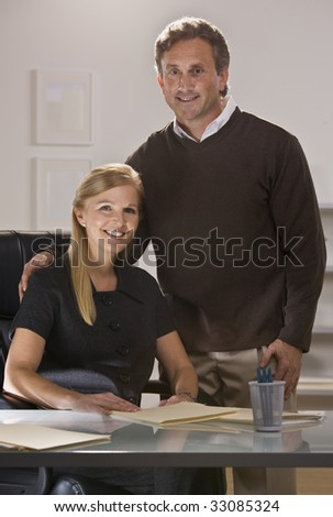 Attractive couple at office with man standing over woman sitting at desk, looking at camera. Vertical.