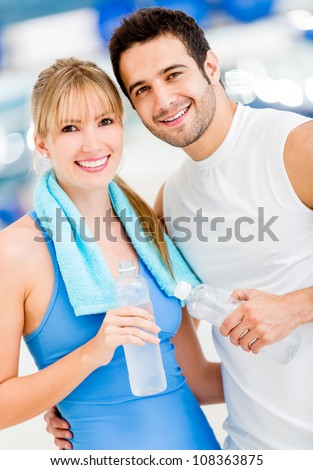 Attractive couple at the gym looking happy - stock photo
