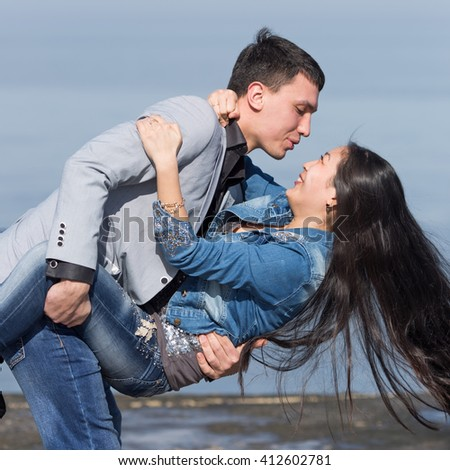 Attractive couple at the sea. European guy carrying  his asian girl - stock photo