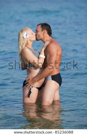 Attractive couple at the sea. Middle aged man and young pregnant woman in sea - stock photo