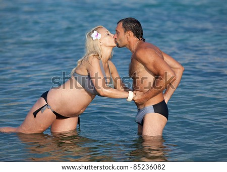 Attractive couple at the sea. Pregnant woman kissing her husband