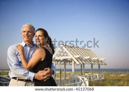 Attractive couple embrace on the beach with arbor in background. Horizontal shot. - stock photo