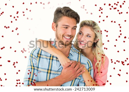 Attractive couple embracing and smiling against red love hearts - stock photo