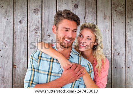 Attractive couple embracing and smiling against wooden planks - stock photo