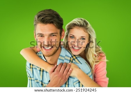Attractive couple embracing and smiling at camera against green vignette - stock photo