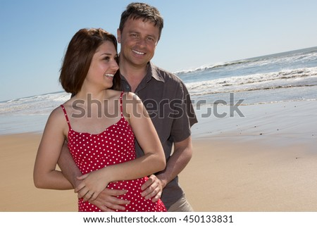 Attractive couple embracing on beach on a sunny day