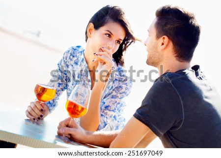 Attractive couple enjoying a romantic date sitting drinking wine in the sunshine at an outdoor table looking lovingly into each others eyes on a high key background - stock photo