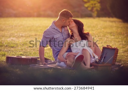 Attractive Couple Enjoying Romantic Sunset Picnic in the Countryside / Vintage style photo with custom white balance, color filters, strong but beautiful lens flare, and some fine film grain added - stock photo