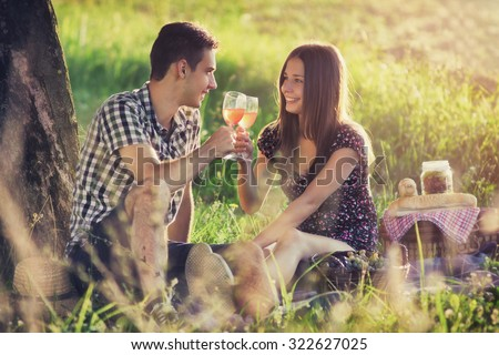 Attractive Couple Enjoying Romantic Sunset Picnic in the Countryside / Vintage style photo with custom white balance, color filters and soft focus effect,  - stock photo