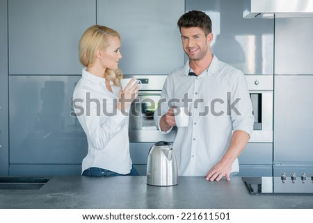 Attractive couple enjoying their early morning coffee standing together in the kitchen chatting with their mugs in their hands - stock photo