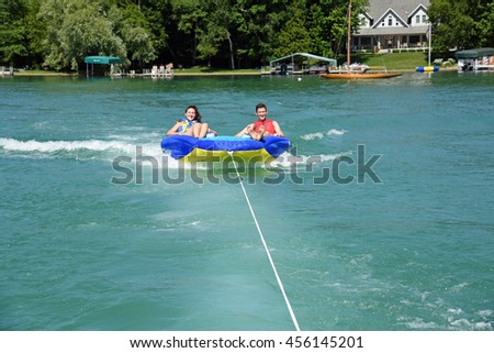 Attractive couple enjoying tubing behind a boat on the lake.