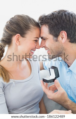 Attractive couple getting engaged on the sofa at home in the living room - stock photo