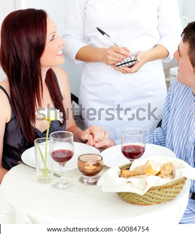 Attractive couple having dinner at the restaurant with waiter taking their order - stock photo