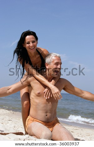 Attractive couple having fun on the beach - stock photo