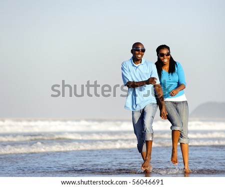 Attractive couple having fun together at the beach - stock photo