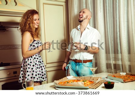 Attractive couple having party fun, drinking, laughing at home party. Celebrate, disco, party, nightlife, entertainment, friendship concept. - stock photo