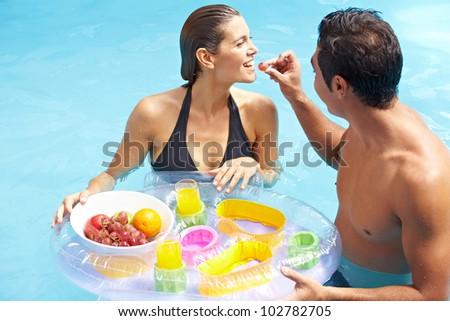 Attractive couple having romantic breakfast in swimming pool - stock photo