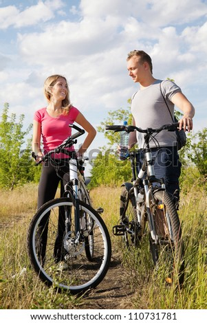 Attractive couple holding bicycles and drinking water in the forest - stock photo