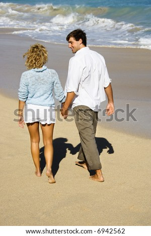 Attractive couple holding hands walking on beach smiling at eachother in Maui, Hawaii. - stock photo