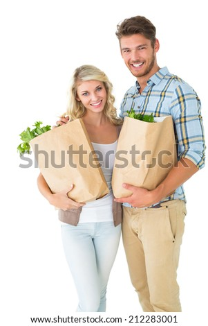 Attractive couple holding their grocery bags on white background - stock photo