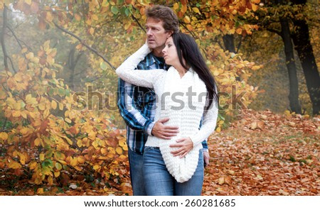 Attractive couple in a autumn park - stock photo